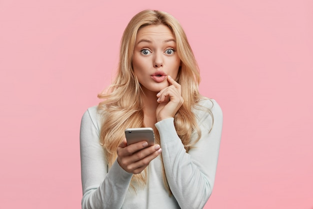 Beautiful blonde woman with white shirt holding phone
