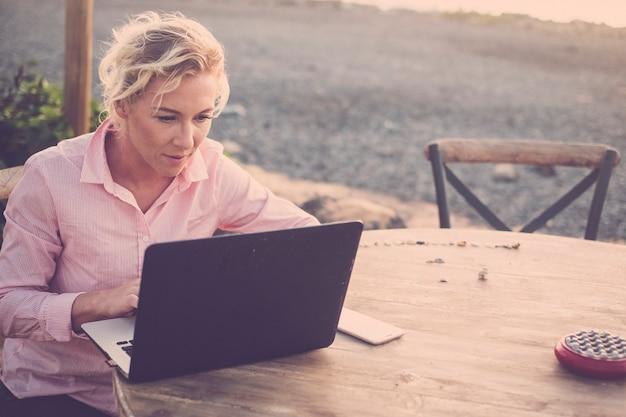 Красивая блондинка работает на ноутбуке на открытом воздухе, сидя и используя беспроводную интернет-технологию для управления своим бизнесом в интернете - альтернативный стиль офисной работы везде - современные люди тысячелетия -