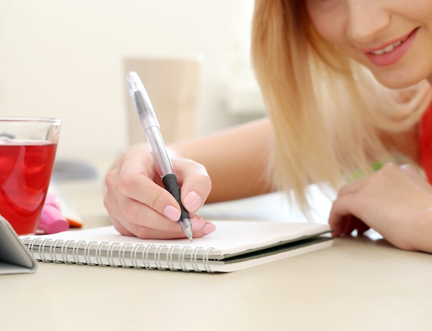 Beautiful blonde woman writing on a notepad