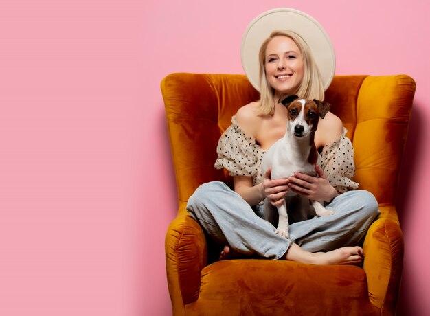 Красивая белокурая женщина с собакой в кресле на розовой стене