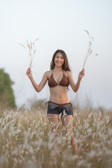 夏の夜に白い花と茶色の牧草地に茶色のビキニで美しい金髪の女性