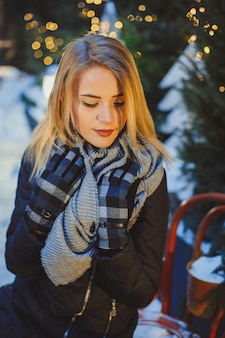Beautiful blonde young caucasian woman in black coat and scarf