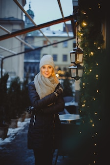 Beautiful blonde young woman in black coat and scarf