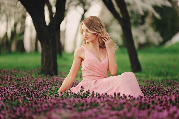 色とりどりの花で美しい金髪の若い女性。春の開花公園でピンクのドレスでメイクや髪型を持つ少女。ロマンチックな女性の芸術作品。