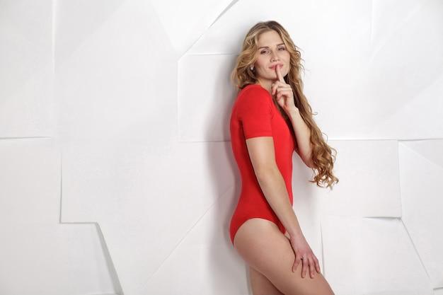 회색 배경 포즈에 빨간 몸에 아름 다운 금발의 젊은 여자