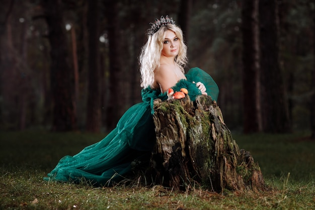 A beautiful blonde young woman in a long green dress and a diadem on her head in the forest.