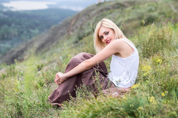 Beautiful blonde young woman sitting on green grass
