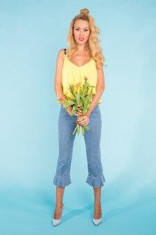 Красивая белокурая молодая женщина, стоящая с букетом желтых тюльпанов на голубой поверхности.