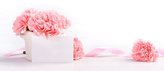 Beautiful blooming baby pink tender carnations in a white vase isolated on bright background, close up, copy space