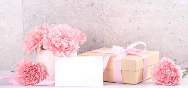 きれいな顔の灰色の背景の机の上に分離されたピンクのリボンボックスと美しい咲くカーネーション、クローズアップ、コピースペース