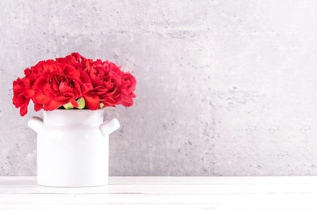 공정한 얼굴 회색 배경 책상에 고립 빨간 리본 상자와 아름 다운 피 카네이션, 가까이, 복사 공간