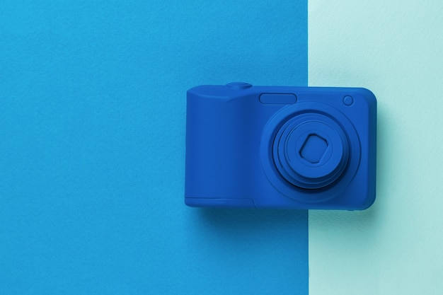 Beautiful blue camera on a two-color background. stylish equipment for photo and video shooting.