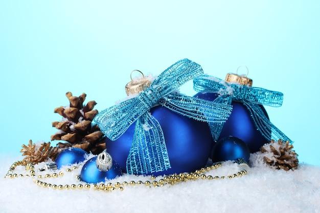 Красивые синие новогодние шары и шишки на снегу на синем фоне