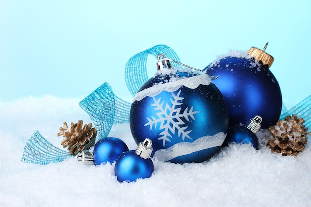 Beautiful blue christmas balls and cones in snow on blue background