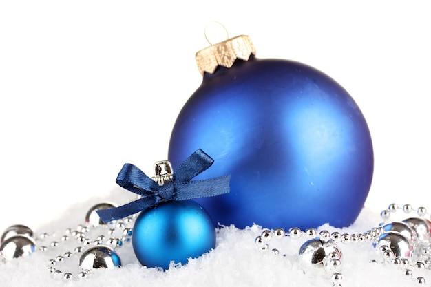 雪の上の美しい青いクリスマスボール、白で隔離