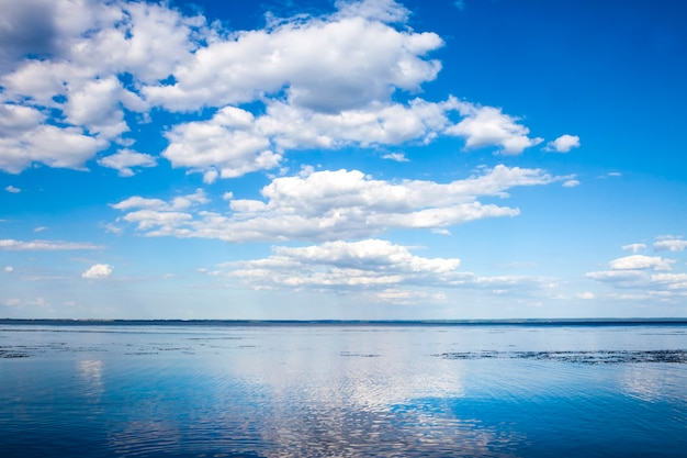 Beautiful blue cloudy sky and its reflection in water of kaniv reservoir, ukraine