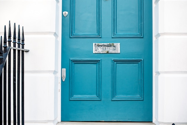 Beautiful blue door with letterbox in a white house facade in notting hill