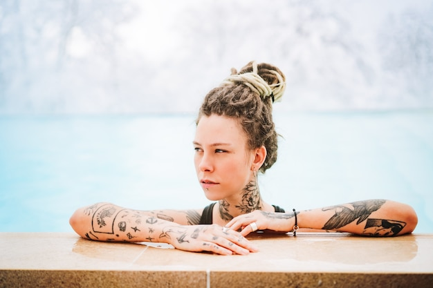 Beautiful blue-eyed androgynous girl with dreadlocks and tattoos in a warm pool against the backdrop of snowy mountains