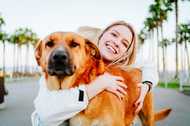 Beautiful blue-eyed blonde in a white windbreaker hugs a big beautiful red dog against the background of palm trees