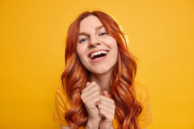 Beautiful blue eyed cheerful woman has red wavy hair keeps hands together smiles broadly enjoys leisure time listens music in stereo headphones with good sound quality