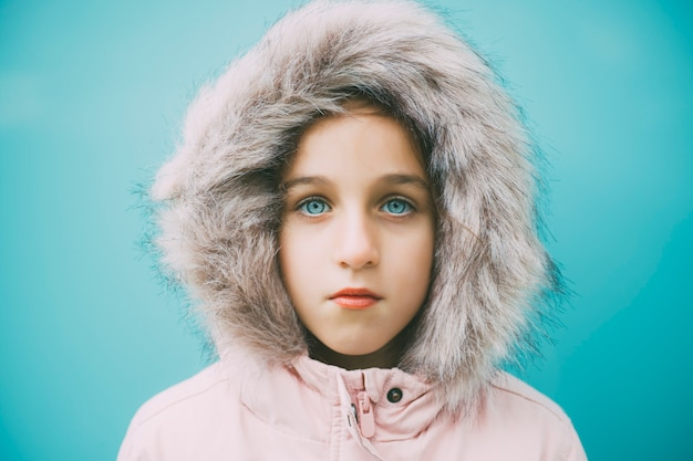 Beautiful blue-eyed child staring with a pink coat