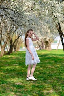 フラワーガーデンを歩いている白いドレスを着た長いブロンドの髪を持つ美しい青い目の女の子。夏と春の明るく感動的な写真。