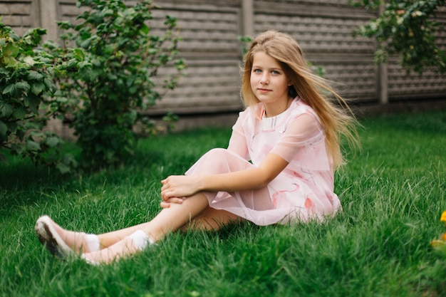 Beautiful blue-eyed girl with long blond hair. little girl in a pink flamingo dress. summer bright, emotional photo.  girl model with long hair sits on green grass