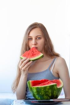 ストラップ付きの灰色のタンクトップで、長い薄茶色の髪の美しい青い目の女の子は、赤いスイカを食べます。