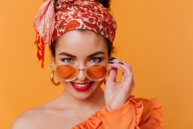 Красивая голубоглазая дама в необычной повязке на голову и красной помаде снимает солнцезащитные очки и позирует на оранжевом пространстве.