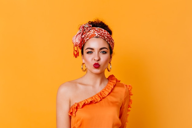 Beautiful blue-eyed woman in orange silk outfit and stylish headband blows air kiss on isolated space.