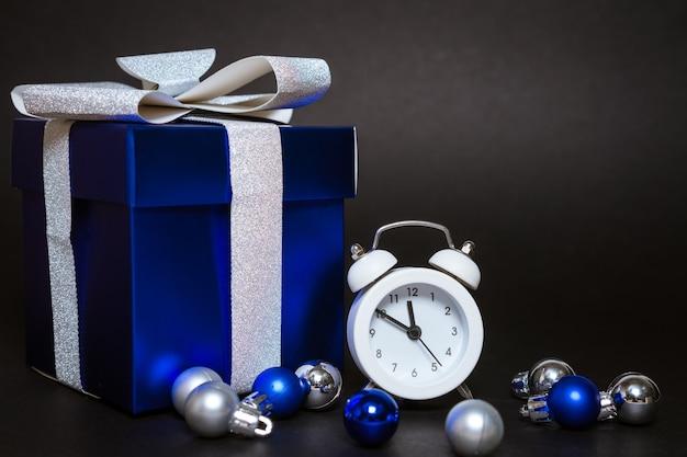 Красивая синяя подарочная коробка и белый будильник с елочными шарами на черном фоне