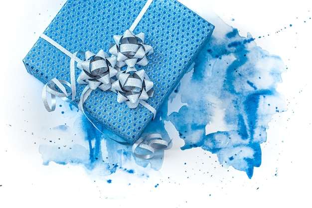 Beautiful blue gift box on watercolor background, stylish creative background.