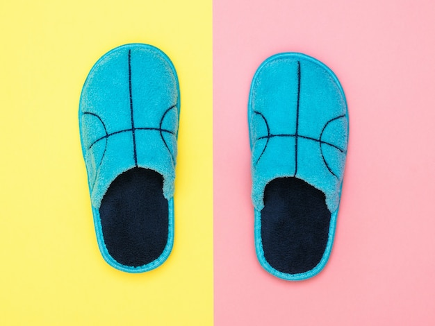 Beautiful blue house slippers on pink and yellow surface. comfortable home shoes. flat lay.