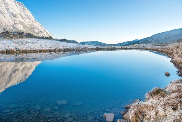 山の中の美しい青い湖、朝日。雪と凍った自然のある風景