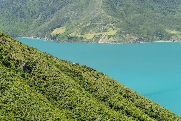 ニュージーランドの緑豊かな山々に囲まれた美しい青い湖