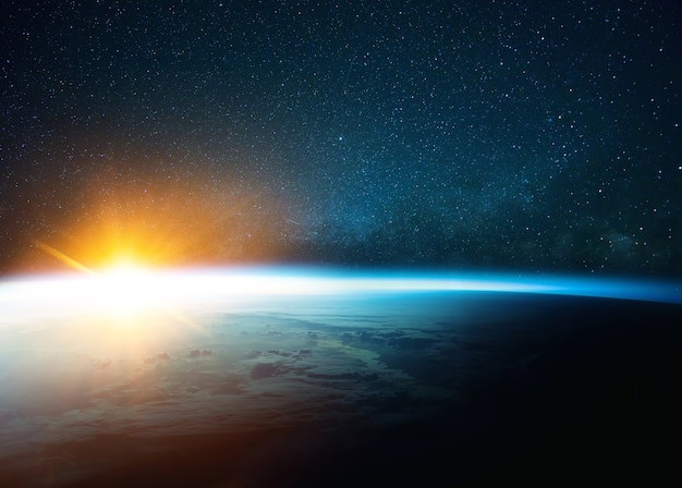 Beautiful blue planet earth in outer space on background of stars and milky way with sunrise. amazing yellow sunset from space. world with sunlight