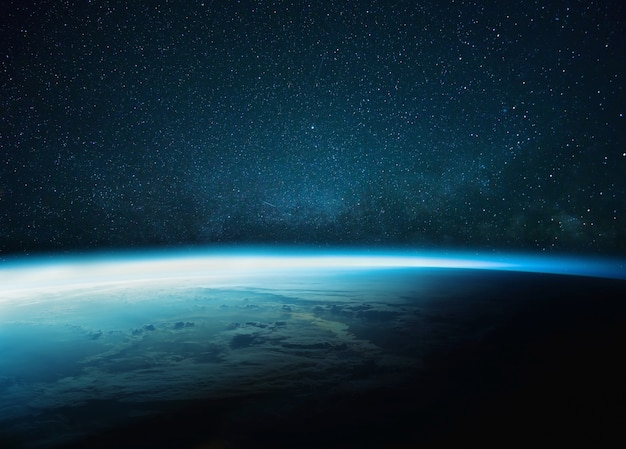 Beautiful blue planet earth with blue glow with starry and milky way. sunrise in space