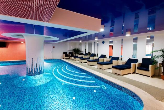 Красивый голубой бассейн с местами для отдыха