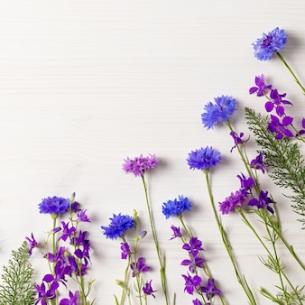 Beautiful blue and purple flowers frame flat lay on white wooden desk, copy space, top view