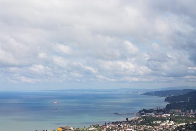 白い巻雲を背景にしたバトゥミの美しい青い海岸。旅。
