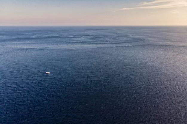 Beautiful blue sea horizon with evening sky and ship