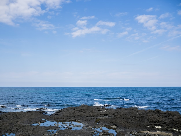 Beautiful blue sea with black sand beach and sky of jeju island in korean