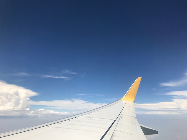 Beautiful of blue sky above the clouds with wings of the airplane