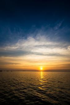 日没時の美しい青い空と海岸の動きのぼやけた雲