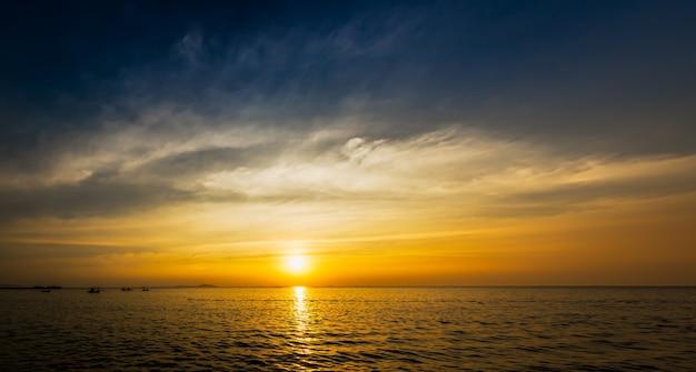 日没時間とモーションの美しい青い空が海の海岸で雲をぼかし