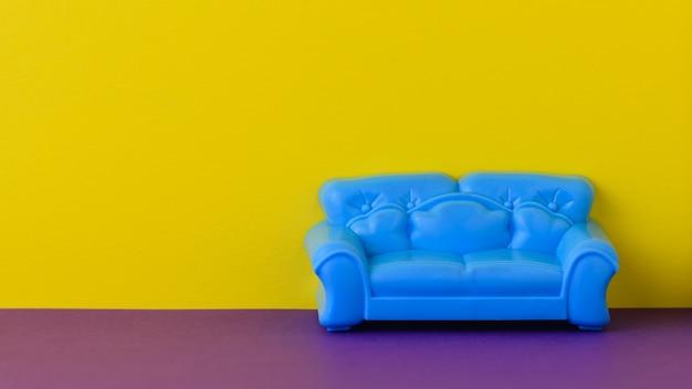 Красивый синий диван на фиолетовом полу у желтой стены.