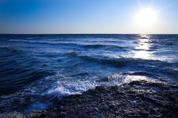 夏の日のクリミア半島の黒海の岩の多い海岸線上の美しい青い夕日と水の石