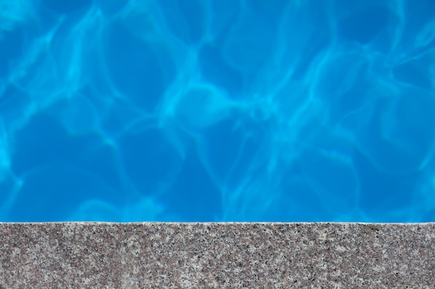Beautiful blue water background transparent clean pool water with part of granite rim with light ref...