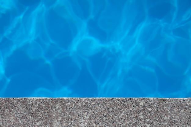 Красивый голубой фон воды прозрачная чистая вода бассейна с частью гранитного ободка с легким реф ...
