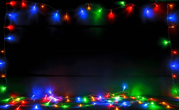 Beautiful blurred christmas with a lot of colorful lights on wooden desk